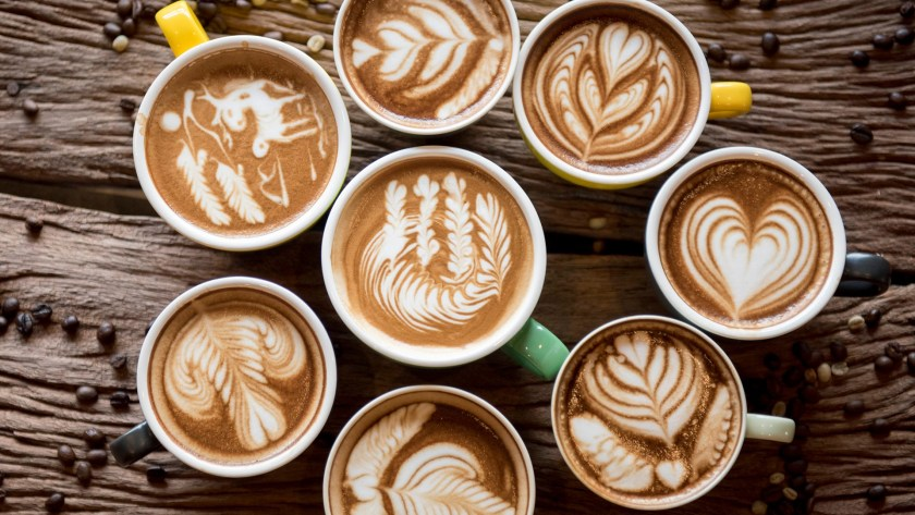 a crowd of mugs with latte drinks in them arranged aesthetically on a table