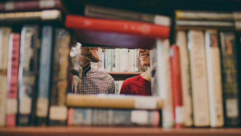 Picture of two people laughing through bookshelf