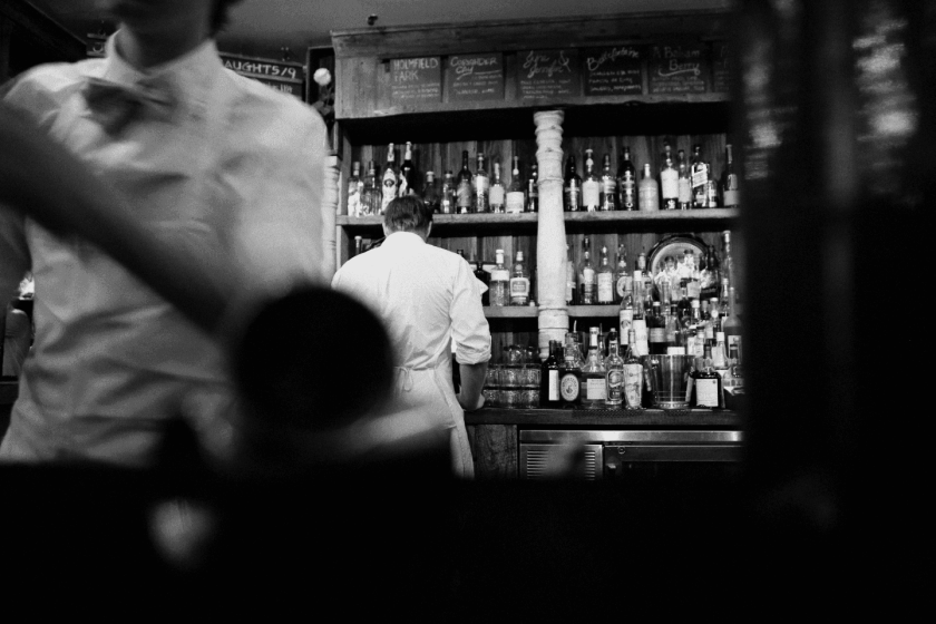 Black and white picture of restaurant, with bartender in the background