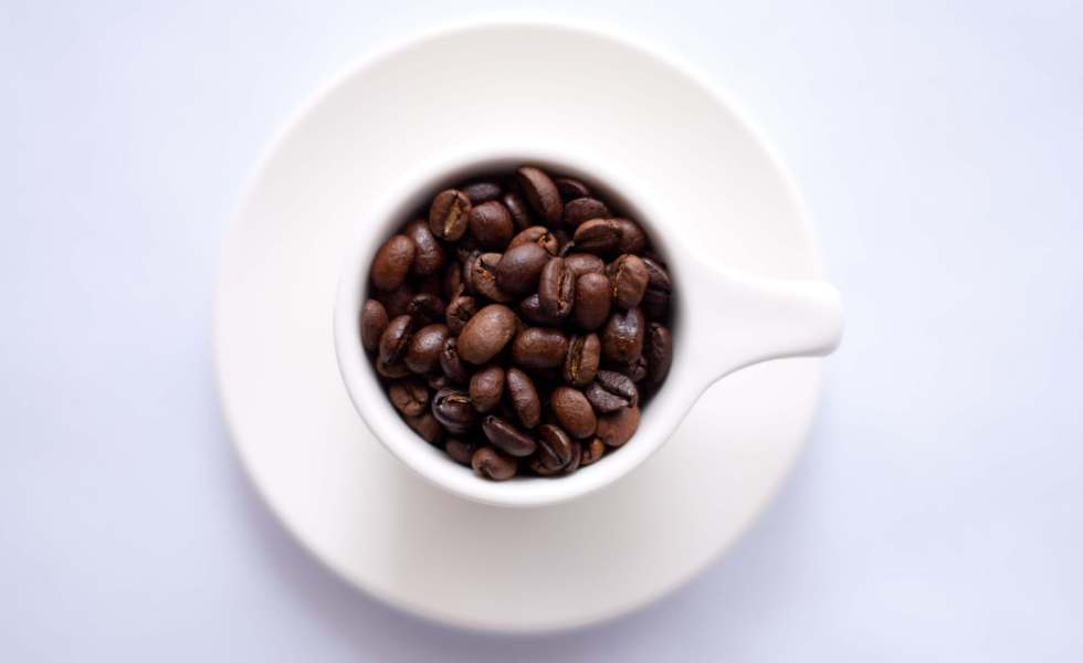do youlove coffee post with a cup of coffee beans against white background