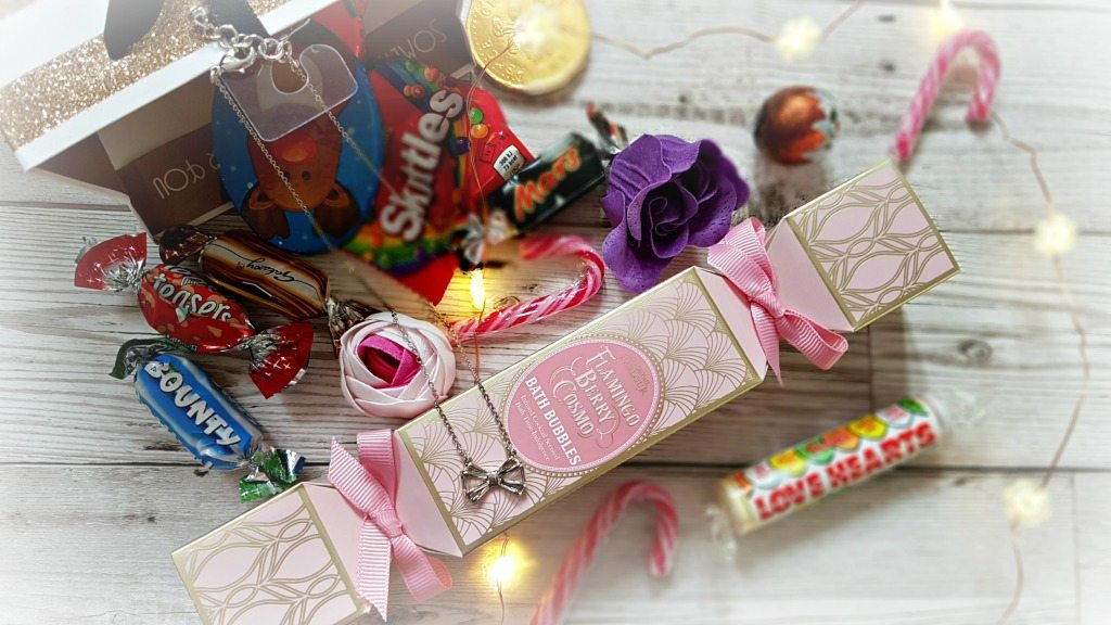 gift bag with sweets, bath products and a silver bow necklace surrounded by led lights on copper wire