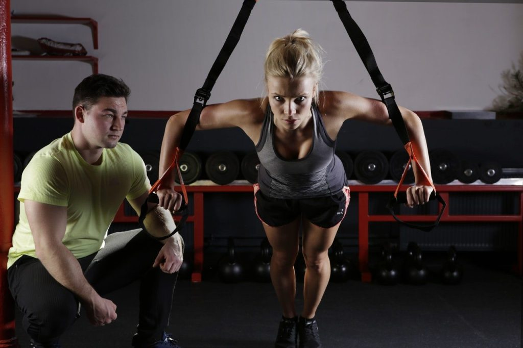 woman using gym equipment with a male personl trainer - getting healthier