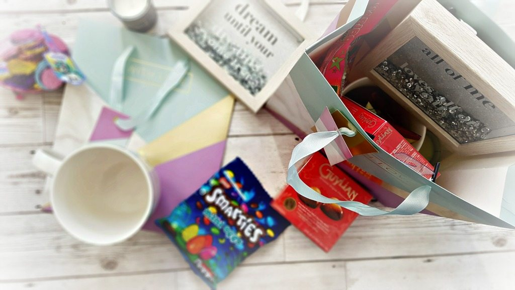 a gift bag laying flat closed with a selection of gifts and chocolates next to an open bag filled the same gifts.