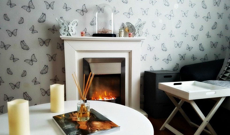 a room with a white fireplace, white round table and butterfly sketch wallpaper with candle and light accessories on the fireplace