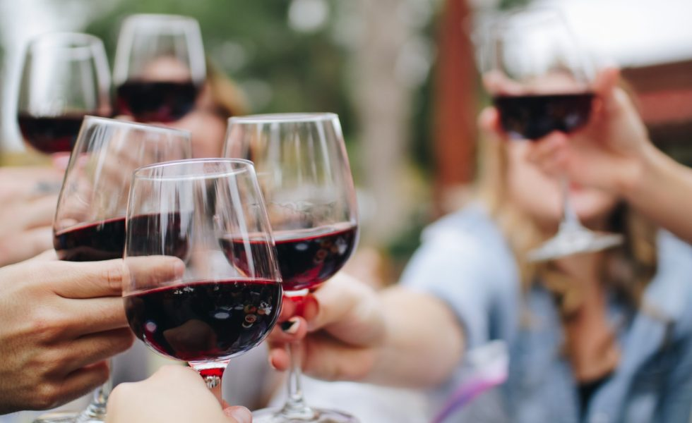 people holding wine glasses in a toast with red wine in glasses