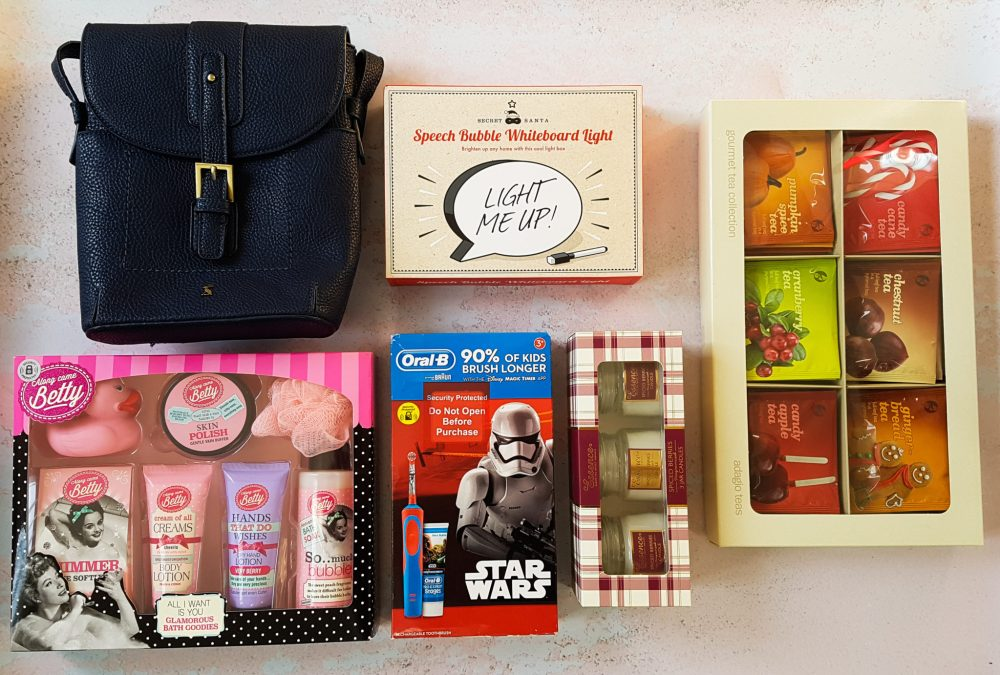 a flatlay of items including a joules handbag, a speech bubble white board light, adagio teas, a star wars electric toothbrush and candles