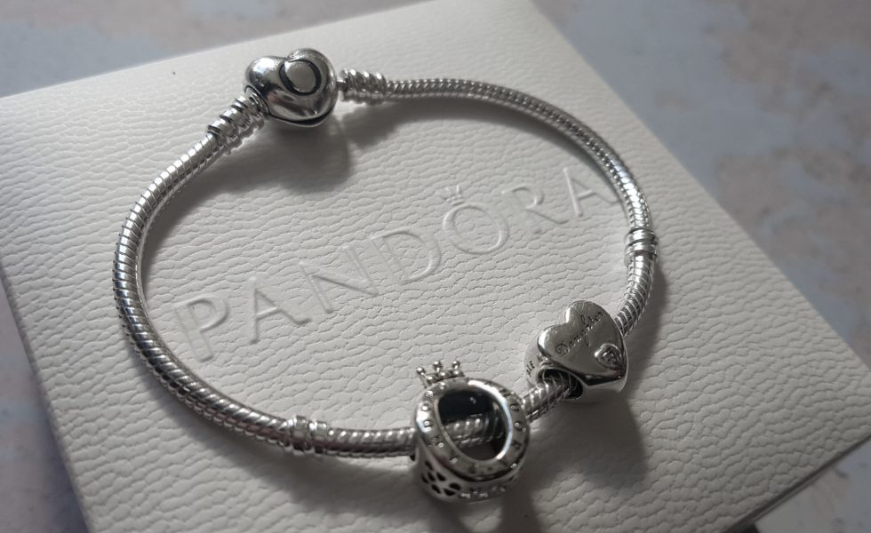 a silver pandora charm bracelet with 2 charms on a white pandora branded box