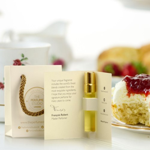image of a perfume sample in a piece of card with a jam and cream scone in the background