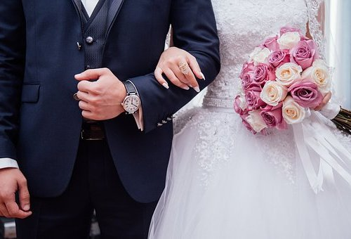 couple linking arms in wedding attire holding a pink bouquet