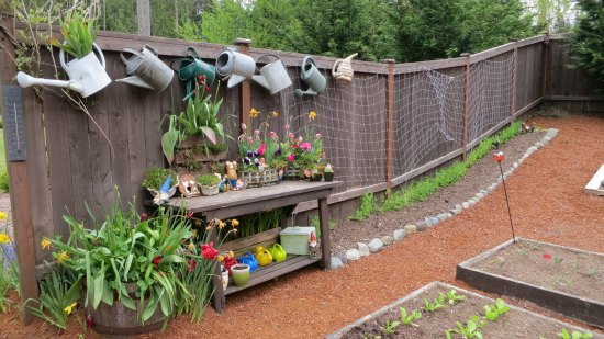 potting bench with flowers old watering cans