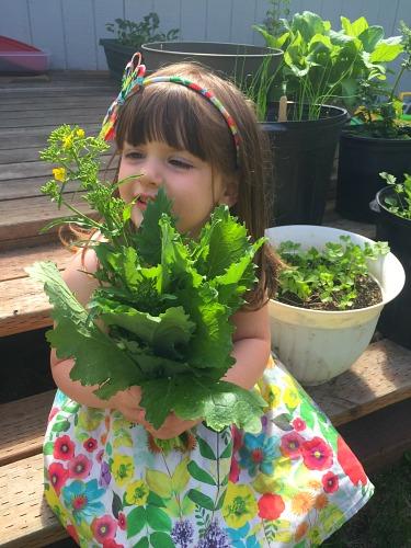 girl holding garden vegetables