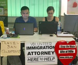 "A photo of two attorneys working on laptops at a folding table at the LAX airport clinic, with signs that say ""travel ban questions?"" and ""volunteer immigration attorney here to help"""