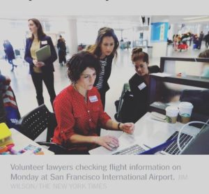 Photo of OneJustice staff around a laptop at a desk at SFO airport.