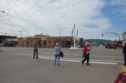People standing in the street to take photos of the mile zero marker.
