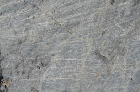 Rock faces have these characteristic scratches from gravel and rock that has been dragged across in the ice.