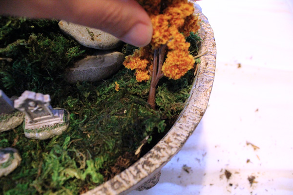 Inserting miniature trees into the moss.