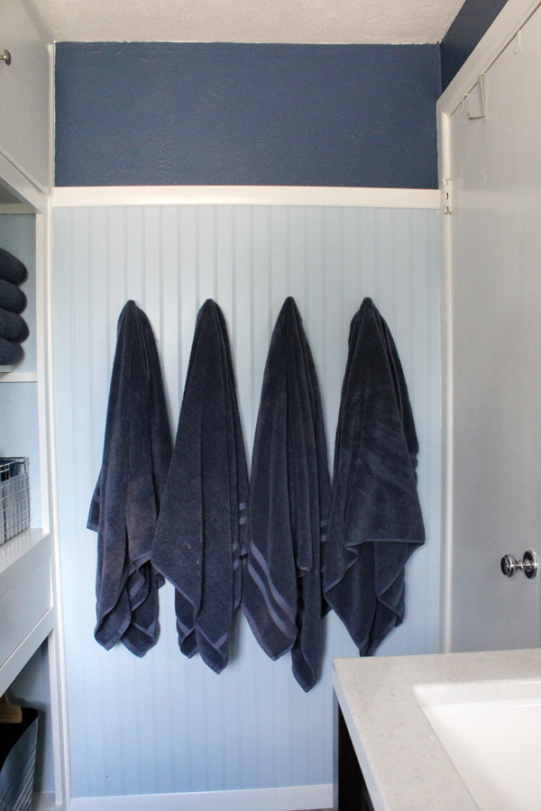 bathroom remodel: navy towels hanging on a light blue and dark blue wall