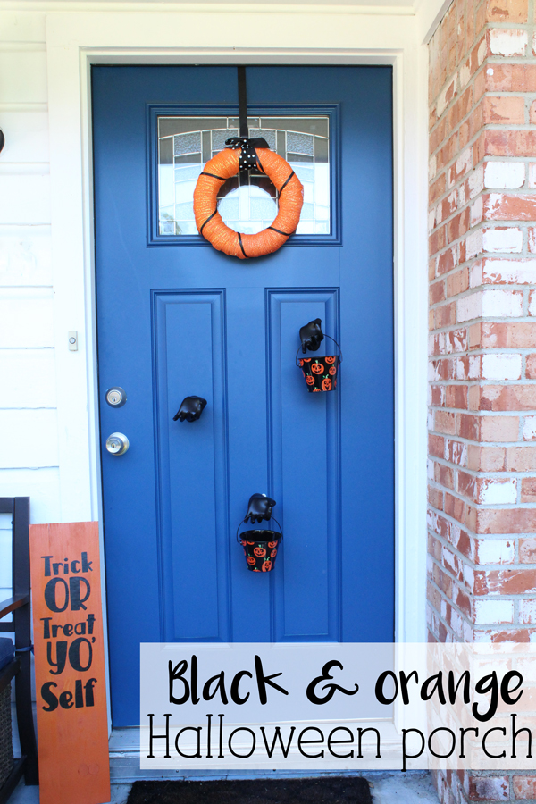 Black and orange Halloween porch tutorial: wreath, sign, and mannequin hands holding bucket of candy
