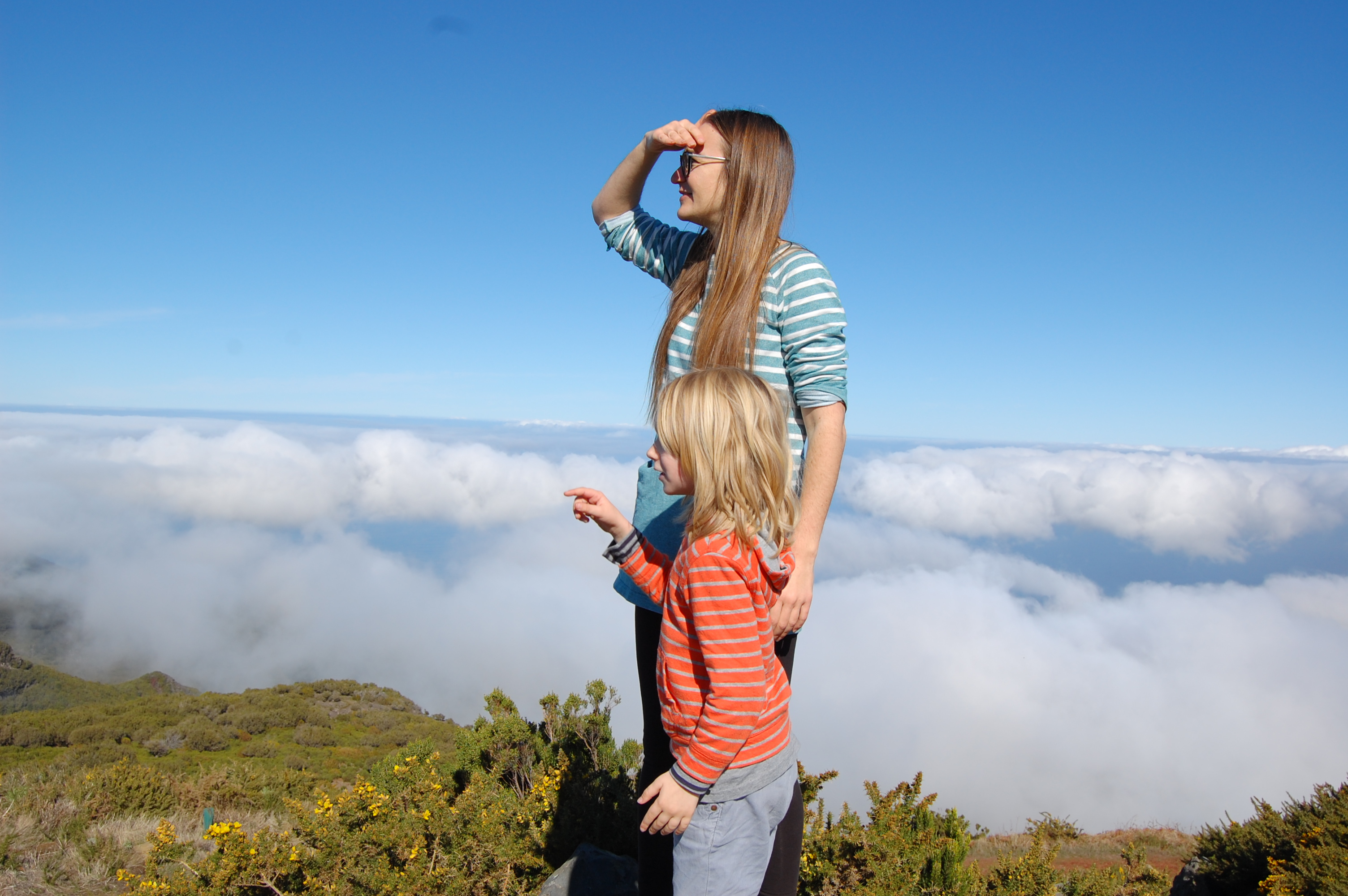The author and her son standing on top of a mountain in Madeira with blue sky above and clouds below