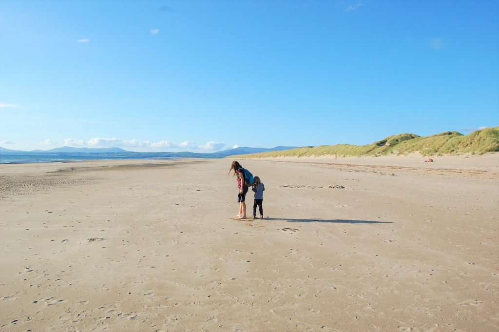 The author and her son standing on a beach in North Wales on a sunny day to illustrate the point that it is possible to live well as a one income family.