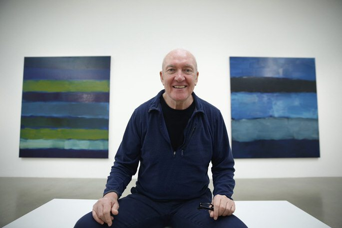 """Artist Sean Scully poses with his works """"Landline BrAYke 5.14"""" (L) and """"Landline Blue Blue"""" at the Timothy Taylor Gallery in London November 20, 2014. REUTERS/Luke MacGregor (BRITAIN - Tags: ENTERTAINMENT SOCIETY)"""