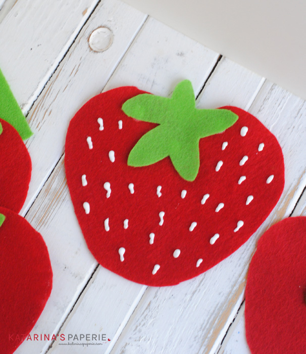 Glue strawberries onto ribbon to make a bunting