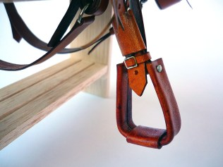 Tan saddle with embossed flame detail - closeup of stirrup
