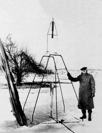 DR. ROBERT H. GODDARD AND LIQUID OXYGEN-GASOLINE ROCKET IN THE FRAME FROM WHICH IT WAS FIRED MARCH 16, 1926 AT AUBURN, MASS. THIS WAS THE FIRST FLIGHT OF A LIQUID PROPELLED ROCKET.   2