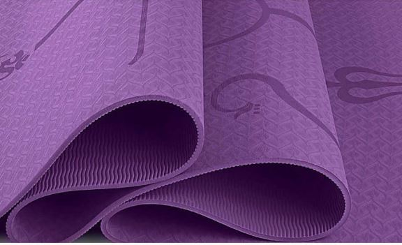 Rolled purple yoga mat showing thickness
