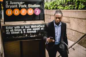 young black male in office suit using cellphone on street
