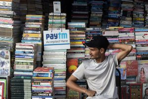 An Indian Book Seller Sits Next to a Sign Indicating That Paytm Mobile Phone Payment Technology is Accepted to Receive Payment From Customers Due to Lack of Indian Currency Notes in a Market in Mumbai India 28 November 2016