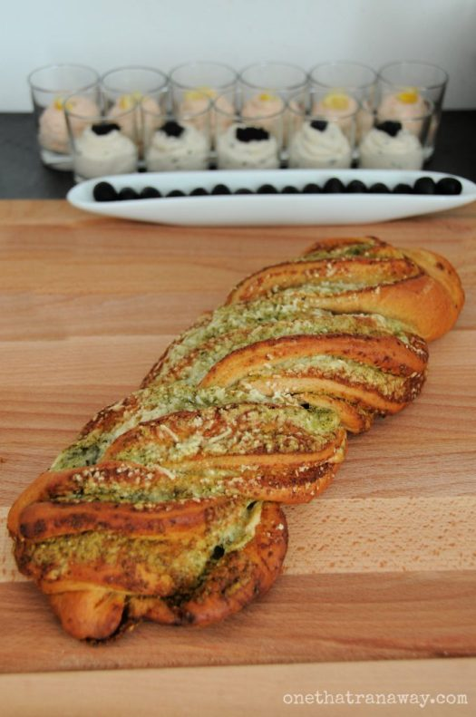 braided pesto bread on a wooden board