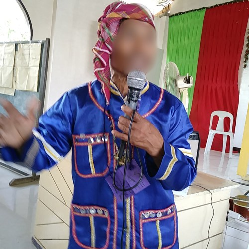 The tribal leader holding a microphone, testifying about how songs are important to their culture.