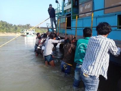 Hin und wieder ist in der Trockenzeit der Wasserstand sehr niedrig, alle packen kräftig an, um das Boot von der Sandbank zu befreien. Ich dann auch, aber erst nach dem Foto :-)