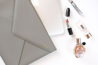 On her desk document folder with laptop and makeup items
