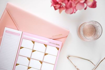 Pink desk planner styled with document folder and water