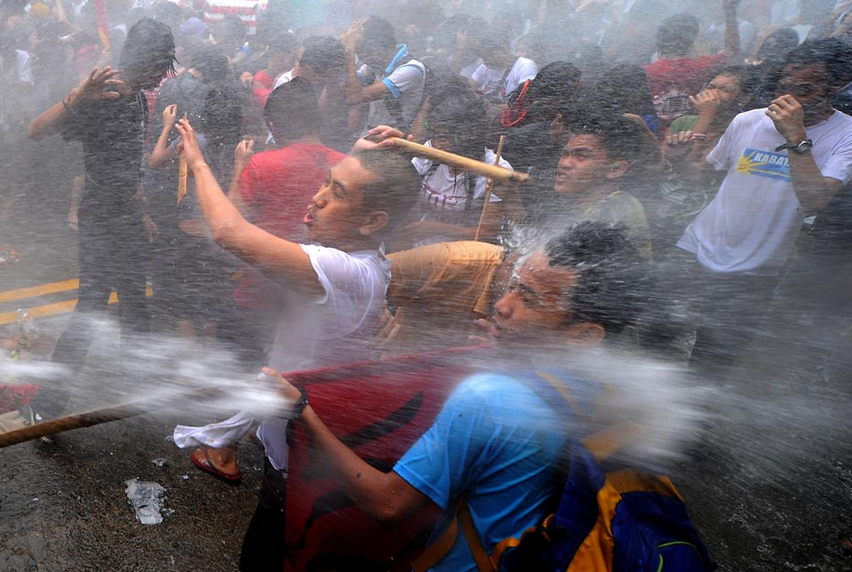 Students protesting decreased university subsidies in the Philippines subjected to water cannon spray