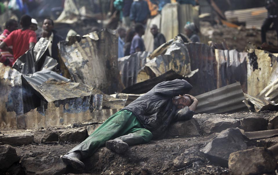 STATE OF SHOCK: Joseph Mwangi, 34, lay in a state of shock after he discovered the charred remains of his two children at the site of a fiery gasoline pipeline explosion that killed dozens in a slum of Nairobi, Kenya, Monday. (Ben Curtis/Associated Press)