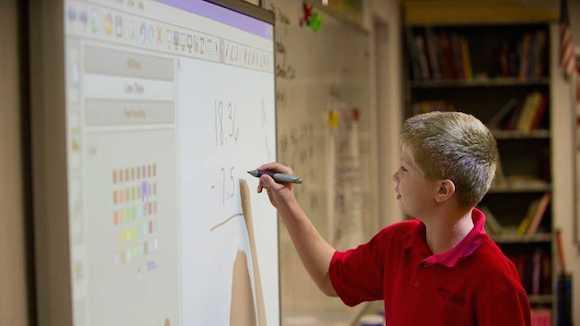 child doing math on whiteboard