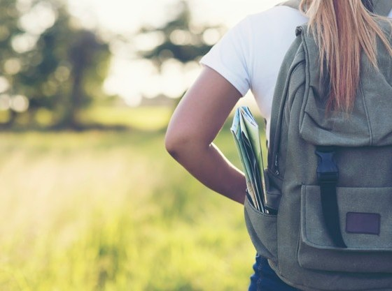 hiking woman with backpack walking gravel road 1150 4285