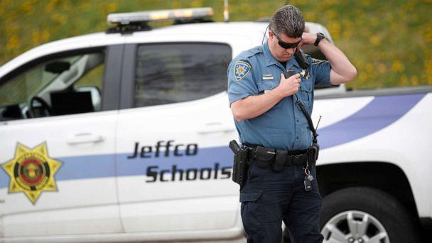PHOTO: An officer from Jefferson County, Colo., Schools listens on his radio as students leave Columbine High School, April 16, 2019, in Littleton, Colo. (David Zalubowski/AP)