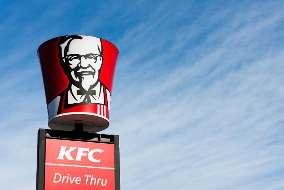Colonel Sanders' image on bucket-shaped sign above KFC franchise