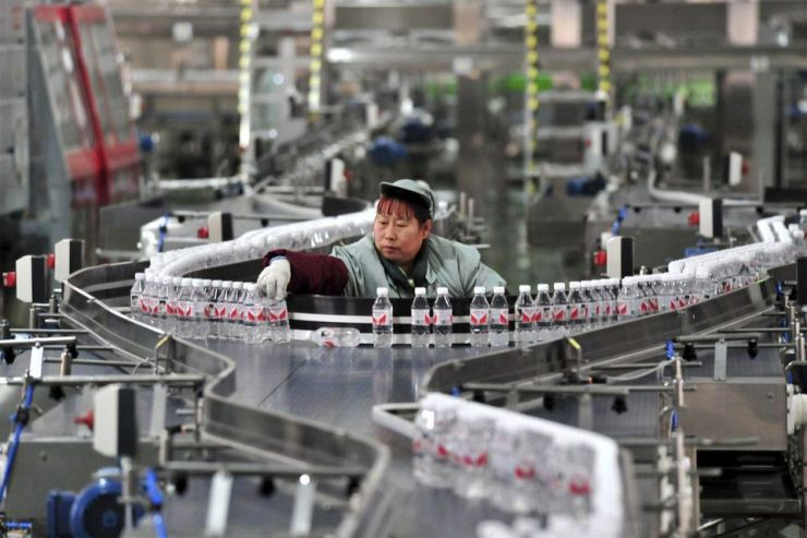 A Chinese worker checks bottles of Wahaha purified water on the assembly line at a factory in... [+] Yichang city, central China's Hubei province.