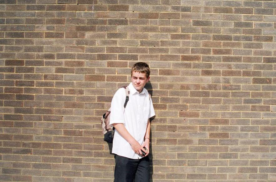 School boy (aged 14) against a brick wall