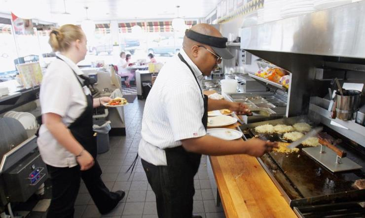 A Waffle House cook prepares a meal on the grill at a location in Norcross, Georgia near the chain's headquarters.