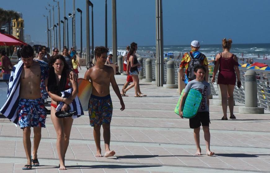 People walk the boardwalk during a spring break at Daytona...
