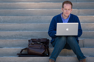 Male student with briefcase sitting on steps and working on a laptop