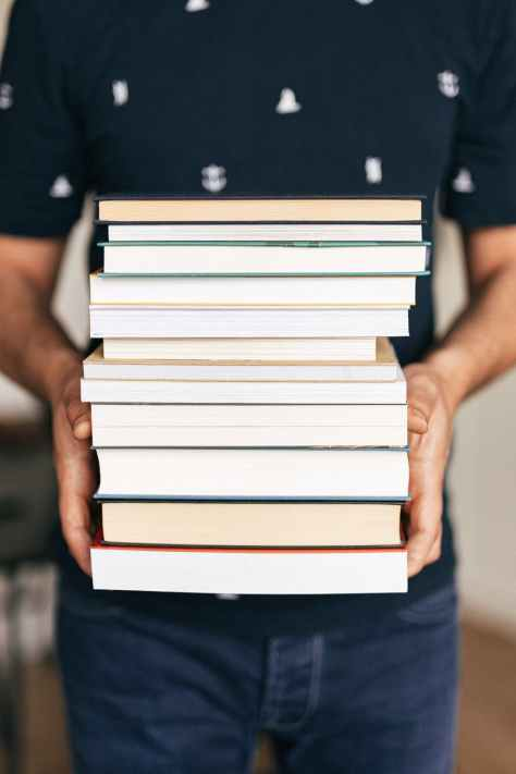 person holding stack of books