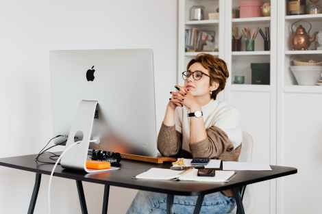 focused female employee reading information on computer in office