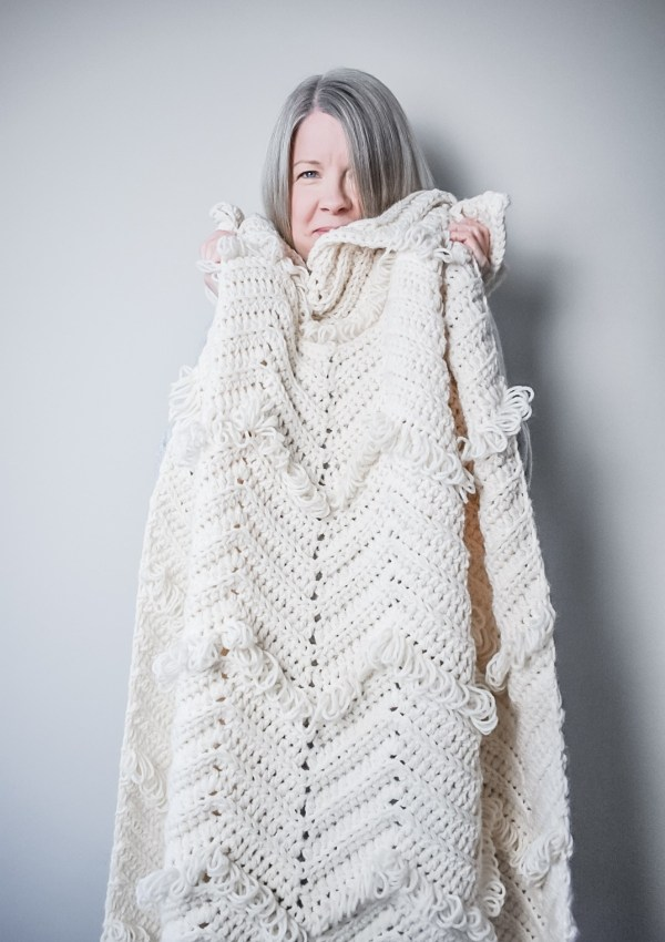 Cream loop stitch blanket held up in a cosy pose